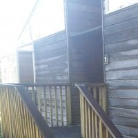 Image of a building showing cedar cladding looking very dark and unkept.